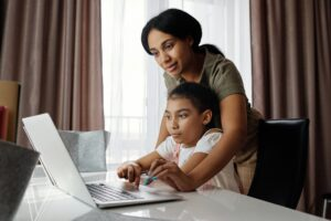 A mother guiding her child while to use a computer.